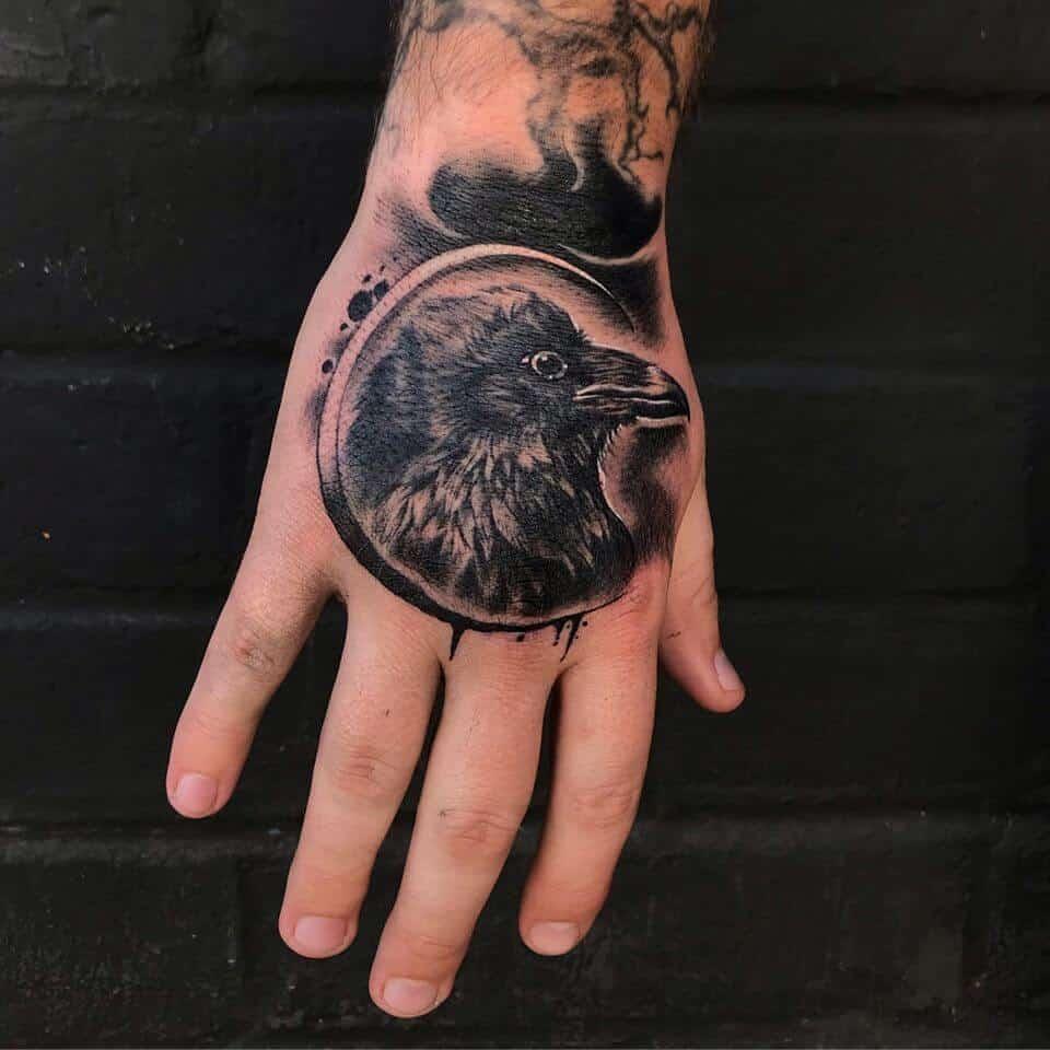 crow raven hand tattoo