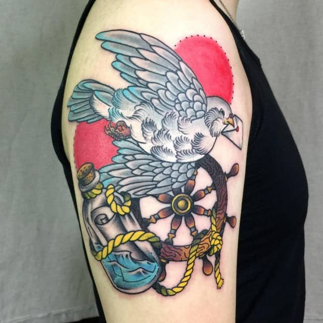 dove and wheel arm tattoo