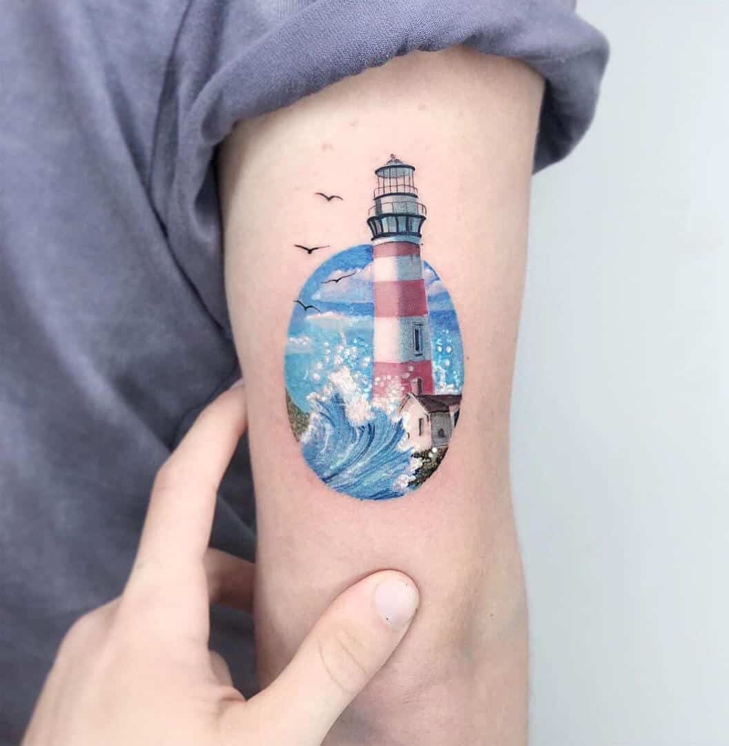 watercolor lighthouse tattoo on arm