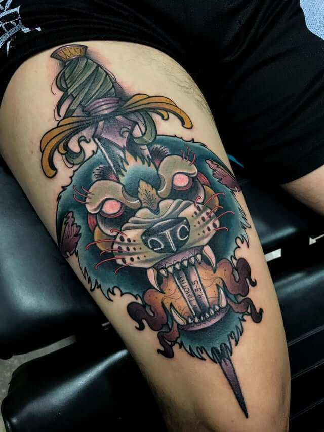 wolf and dagger tattoo on thigh